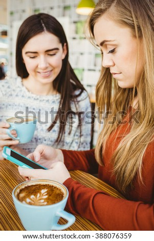 Friends using smartphone and having coffee in a coffee shop - stock photo