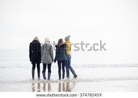 Friends walking along a Beach - stock photo