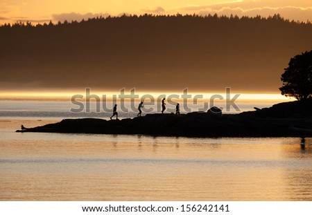 Friends walking along the beach at sunset - stock photo