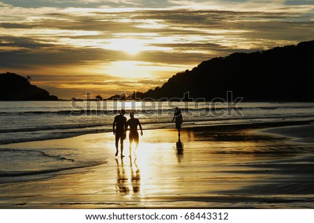 Friends walking at sunset on the beach - stock photo