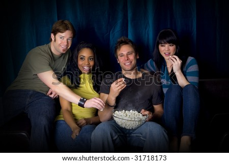 Friends watching a game eating popcorn - stock photo