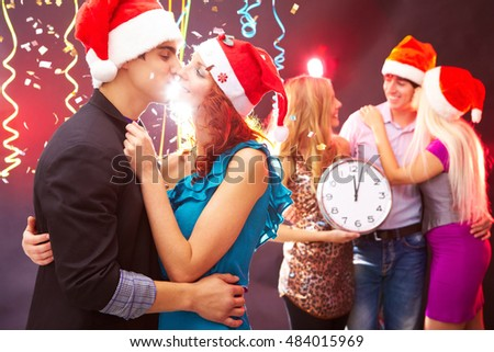 Friends wearing santa hats celebrating new year at nightclub party as clock strikes midnight, loving couple kissing each other tenderly in foreground