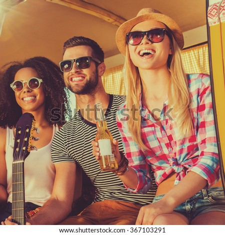 Friends will be friends. Group of young happy people enjoying time together while sitting at their retro minivan - stock photo
