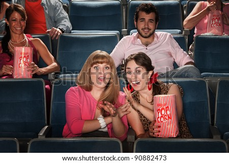 Friends with a bag of popcorn in theater - stock photo