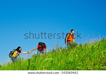 Friends with backpacks on climbing the summer hill