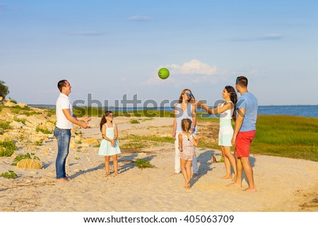 Friends with children playing with the ball on the beach. Summer holiday and family concept