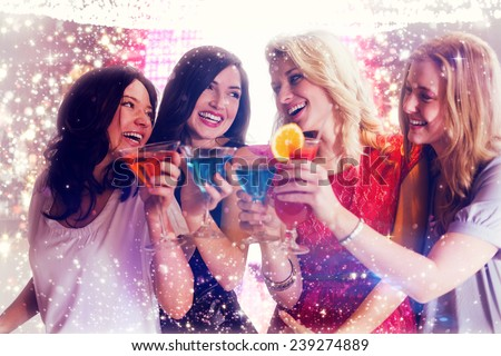 Friends with drinks against gold and red lights - stock photo