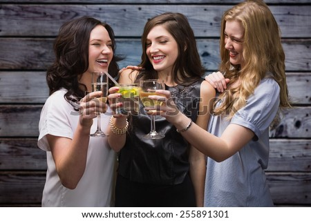 Friends with drinks against grey wooden planks - stock photo