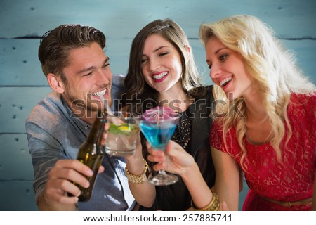 Friends with drinks against painted blue wooden planks - stock photo