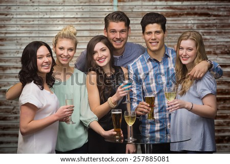 Friends with drinks against wooden planks - stock photo