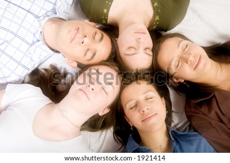 friends with heads together while sleeping on the floor - soft focus - stock photo