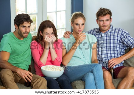 Friends with popcorn and beer watching football match at home - stock photo