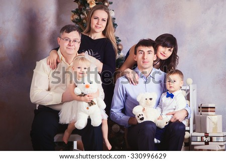 Friends with small children near a festive Christmas tree. Happy Big family holding Christmas presents. Portrait of friendly family looking at camera on Christmas evening - stock photo