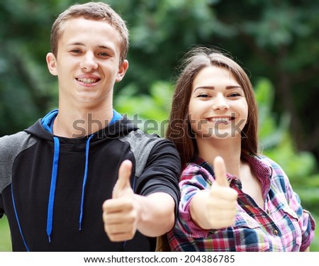 Friends with thumbs up outdoor, teenagers boy and girl students - stock photo