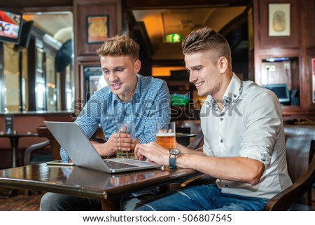 Friends working togetrher. Two businessmen friends men drinking beer and having fun together in the bar and working on the laptop