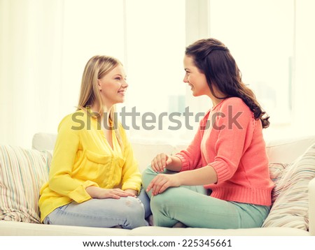 friendship and happiness concept - two girlfriends having a talk at home - stock photo