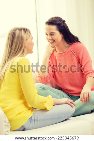 friendship and happiness concept - two girlfriends having a talk at home