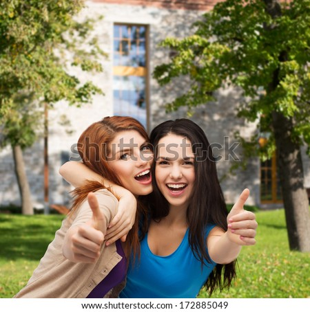 friendship and happy people concept - two smiling girls showing thumbs up - stock photo