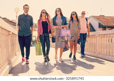 Friendship and shopping concept. Friends walking on the bridge in the city - and three young women with shopping bags. - stock photo