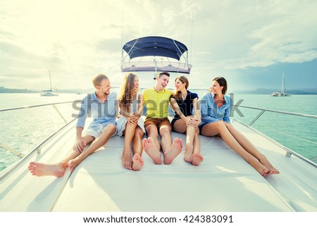 Friendship and vacation. Group of laughing young people sitting on the yacht deck sailing the sea. - stock photo
