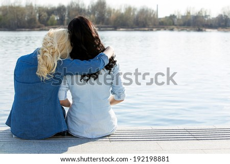 Friendship. Best friends sitting by the river - stock photo