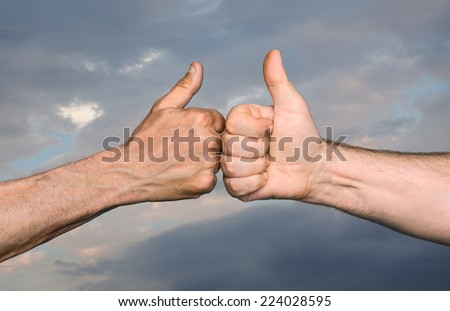 Friendship concept. Two men bumping fists with thumbs up against sky with clouds - stock photo