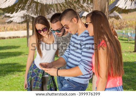 Friendship concept. Young group of friends having fun and playing with mobile phone in the park at beautiful sunny day.