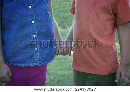 Friendship contest: little boy and little girl holding hands - stock photo