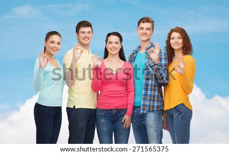 friendship, dream, future and people concept - group of smiling teenagers showing ok sign over blue sky with white cloud background - stock photo