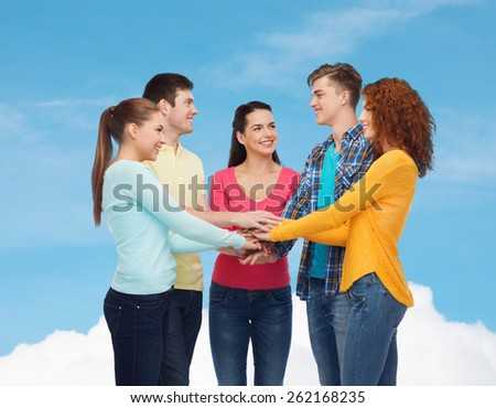 friendship, dream, teamwork, gesture and people concept - group of smiling teenagers with hands on top of each other over blue sky with white cloud background - stock photo