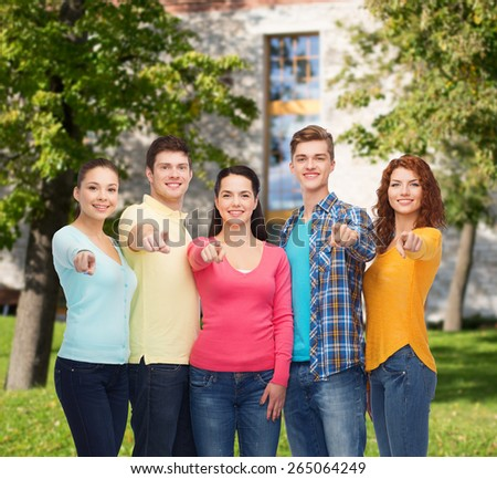 friendship, education, summer vacation and people concept - group of smiling teenagers pointing finger on you over campus background - stock photo