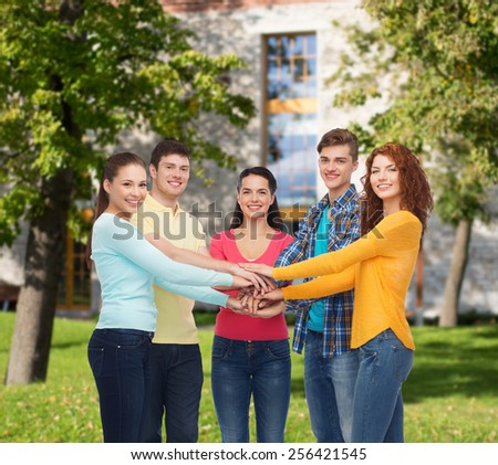 friendship, education, teamwork, gesture and people concept - group of smiling teenagers putting hand on top of each other over campus background - stock photo