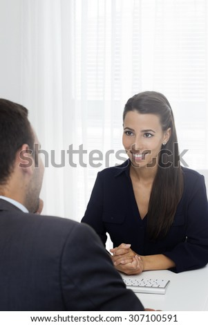 Friendship female well dressed manager sitting at a  desk opposite mature man and talking.  - stock photo