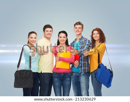 friendship, future, education and people concept - group of smiling teenagers with folders and school bags showing thumbs up over gray background with laser light - stock photo