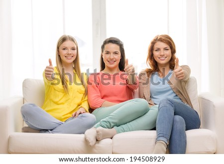 friendship, gesture and happiness concept - three girlfriends showing thumbs up at home