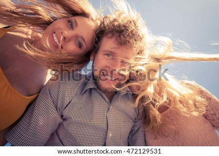 Friendship happiness summer freedom concept. Group of friends boy two girls having fun outdoor wind in hair, joy playful mood, wide angle view