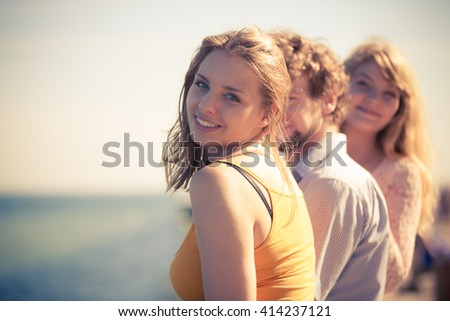 Friendship happiness summer holidays concept. Group of friends boy two girls having fun outdoor enjoying sea breeze sunlight,  joyful mood. - stock photo