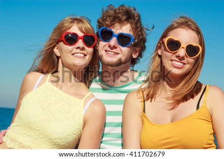 Friendship happiness summer holidays concept. Group of friends boy two girls in colorful sunglasses having fun outdoor against sky,  joy playful mood.