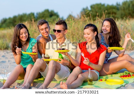 friendship, happiness, summer vacation, holidays and people concept - group of smiling friends sitting beach