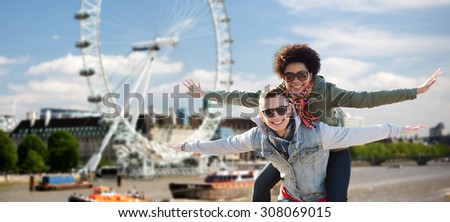 friendship, leisure, international, freedom and people concept - happy teenage couple in shades having fun over london ferry wheel background - stock photo