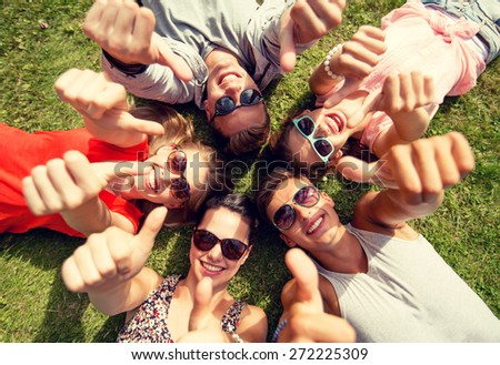 friendship, leisure, summer, gesture and people concept - group of smiling friends lying on grass in circle and showing thumbs up outdoors - stock photo