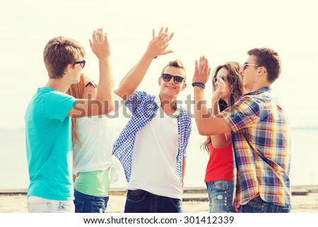 friendship, leisure, summer, gesture and people concept - group of smiling friends making high five outdoors - stock photo