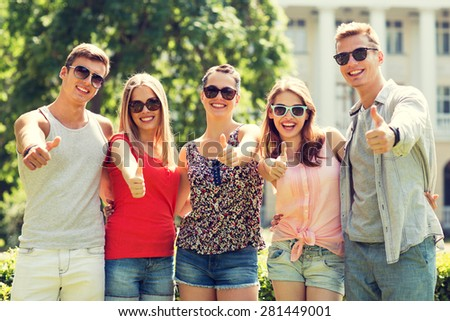 friendship, leisure, summer, gesture and people concept - group of smiling friends showing thumbs up outdoors - stock photo