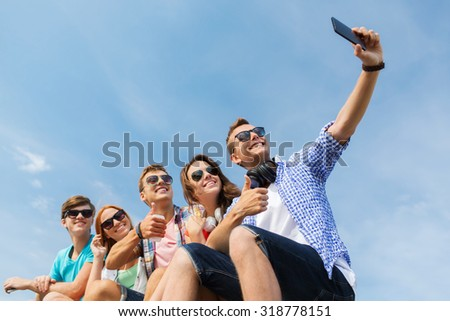 friendship, leisure, summer, technology and people concept - group of happy friends with smartphone taking selfie outdoors - stock photo