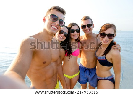 friendship, leisure, summer, technology and people concept - group of smiling friends making selfie on beach - stock photo