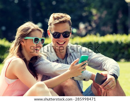 friendship, leisure, summer, technology and people concept - group of smiling friends with smartphone sitting on grass in park - stock photo