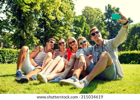 friendship, leisure, summer, technology and people concept - group of smiling friends with smartphone sitting on grass and making selfie in park