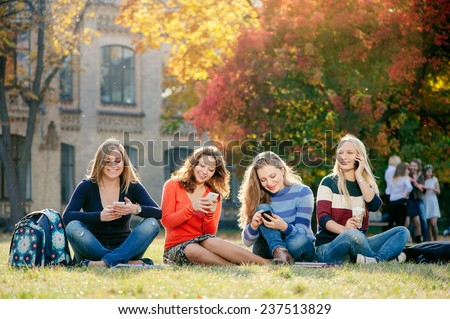 Friendship, leisure, technology and people concept - group of smiling girl friends with smartphones sitting on grass with university building in the background - stock photo