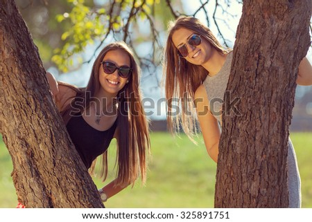 Friendship - lifestyle concept. Group of young and cheerful girls having fun and peeking behind the tree. - stock photo