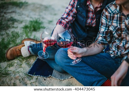 Friendship, love, happiness, summer vacation, holidays and people concept - couple sitting on beach and drinking wine from glasses near bonfire in the evening. Shallow focus. - stock photo